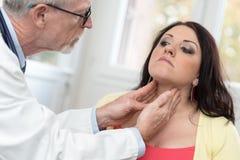 Доктор проверяя тиреоид Стоковая Фотография RF