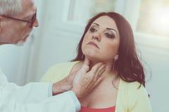 Доктор проверяя тиреоид Стоковое Фото