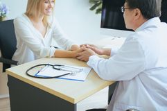 Доктор психолога человека руки успокаивая к счастливому женскому пациенту и давая консультацию и поощрение на больнице стоковое фото rf