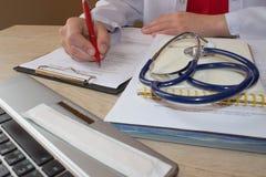 Доктор работая в больнице писать рецепт Таблица деятельности ` s доктора медицины Стоковые Изображения RF