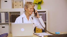 Доктор работая в офисе и получая телефонный звонок сток-видео