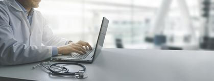 Доктор работая на ноутбуке в современном офисе клиник стоковые фото