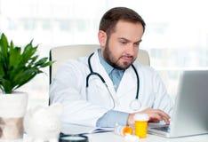 Доктор работая с портативным компьютером Стоковые Изображения RF