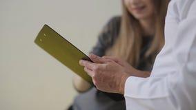 Доктор рассматривает беременную женщину и пишет к медицинской карточке назначения для обработки сток-видео