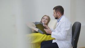 Доктор рассматривает беременную женщину и пишет к медицинской карточке назначения для обработки видеоматериал