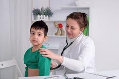 Доктор рассматривает больного школьника ребенка в офисе Стоковая Фотография RF