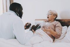Доктор рассматривает пожилой пациент headaches стоковая фотография