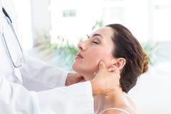 Доктор рассматривая ее челюсть пациентов стоковые изображения rf