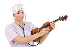 доктор рассматривая женскую скрипку Стоковое фото RF