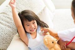 Доктор рассматривая маленькую девочку путем использование стетоскопа стоковые фото