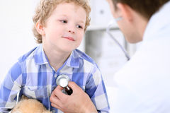 Доктор рассматривая пациента ребенка стетоскопом Стоковые Фото
