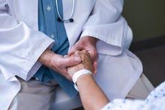 Доктор рассматривая старшего пациента Стоковые Изображения