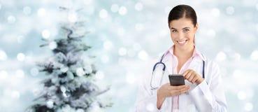 Доктор рождества усмехаясь с умным телефоном на запачканных светах Стоковое фото RF