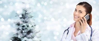 Доктор рождества усмехаясь с умным телефоном на запачканных светах Стоковая Фотография