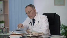 Доктор сидя перед кучей книги думая о теме для его научной работы видеоматериал
