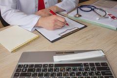 Доктор сидит в медицинском офисе в клинике и пишет историю болезни Doctor& x27 медицины; таблица деятельности s стоковые изображения rf