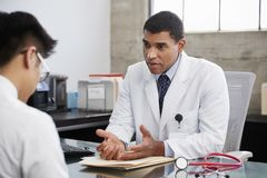 Доктор смешанной гонки Concerned мужской консультируя мужской пациент стоковое фото rf