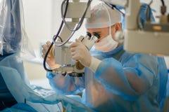 Доктор смотрит через микроскоп, aphtholmologist выполняет деятельность на глазах, ученый рассматривает глаз стоковое фото