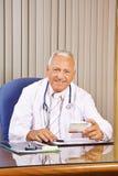 Доктор с лекарством в его офисе Стоковое Фото
