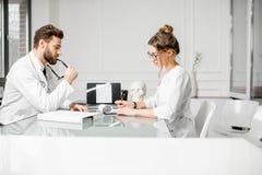 Доктор с женским ассистентом в офисе Стоковые Фото