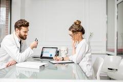 Доктор с женским ассистентом в офисе Стоковая Фотография