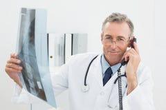 Доктор с изображением рентгеновского снимка используя телефон на офисе Стоковые Изображения