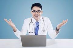 Доктор с компьтер-книжкой и голубой предпосылкой Стоковая Фотография