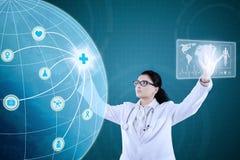 Доктор с медицинским значком на виртуальном экране Стоковая Фотография RF