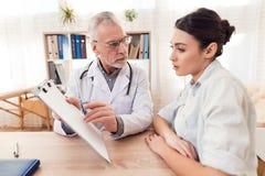 Доктор с стетоскопом и женским пациентом в офисе Доктор говорит диагноз Стоковые Фотографии RF