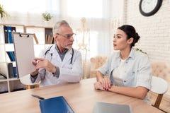 Доктор с стетоскопом и женским пациентом в офисе Доктор говорит диагноз Стоковые Фото