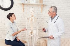 Доктор с стетоскопом и женским пациентом в офисе Женщина говорит симптомы Стоковые Изображения RF