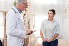 Доктор с стетоскопом и женским пациентом в офисе Женщина говорит симптомы Стоковые Изображения