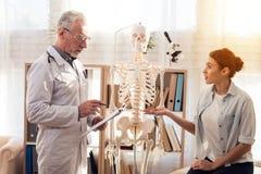 Доктор с стетоскопом и женским пациентом в офисе Женщина говорит симптомы Стоковые Фотографии RF