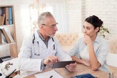 Доктор с стетоскопом и женским пациентом в офисе Доктор использует таблетку Стоковые Изображения