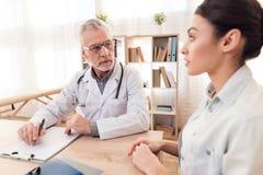Доктор с стетоскопом и женским пациентом в офисе Пациент говорит симптомы Стоковое Изображение RF