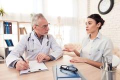 Доктор с стетоскопом и женским пациентом в офисе Пациент говорит симптомы Стоковая Фотография