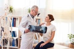 Доктор с стетоскопом и женским пациентом в офисе Доктор показывает рентгеновский снимок бедер Стоковые Фото