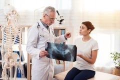 Доктор с стетоскопом и женским пациентом в офисе Доктор показывает рентгеновский снимок бедер Стоковые Фотографии RF