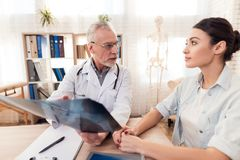 Доктор с стетоскопом и женским пациентом в офисе Доктор показывает рентгеновский снимок к пациенту Стоковое Фото