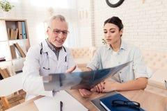 Доктор с стетоскопом и женским пациентом в офисе Доктор показывает рентгеновский снимок Стоковые Фотографии RF