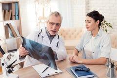Доктор с стетоскопом и женским пациентом в офисе Доктор показывает рентгеновский снимок Стоковое Изображение RF