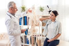 Доктор с стетоскопом и женским пациентом в офисе Терпеливые повреждения шеи ` s Стоковые Изображения RF