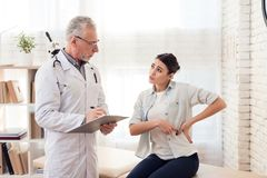 Доктор с стетоскопом и женским пациентом в офисе Терпеливые повреждения стороны ` s Стоковая Фотография
