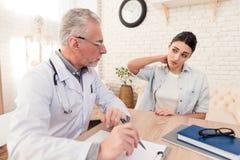 Доктор с стетоскопом и женским пациентом в офисе Терпеливые повреждения шеи ` s Стоковые Фотографии RF