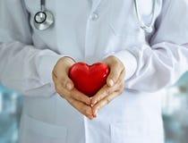 Доктор с стетоскопом и красное сердце формируют в руках на больнице стоковые фото