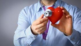 Доктор с стетоскопом рассматривая красное сердце, изолированное на белой предпосылке Стоковая Фотография RF