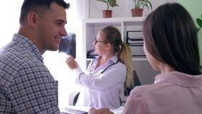 Доктор с хорошими новостями держит рентгеновский снимок в его руке и говорит о здоровье молодой пары в клинике рождаемости сток-видео