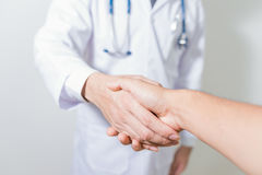 Доктор тряся patient& x27; руки s на белой предпосылке Стоковое фото RF