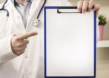 Доктор указывая к доске сзажимом для бумаги с чистым листом бумаги стоковое фото rf
