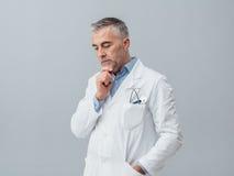 Доктор думая с рукой на подбородке Стоковая Фотография RF